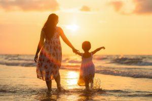 Sonnenuntergang am Strand mit dem Kind am Strand